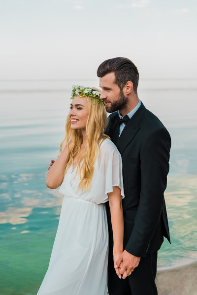 wedding couple in suit and white dress holding hands and looking away on beach